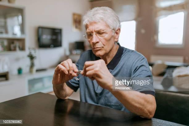 Senior man examining hearing aid