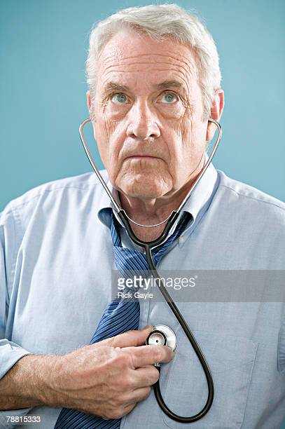 senior man examining himself with stethoscope - hypochondria stock photos and pictures