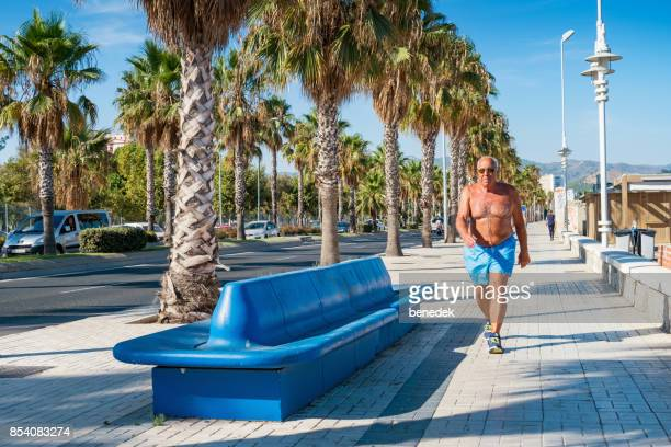 senior man exercises at beach in malaga andalusia spain - shorts stock pictures, royalty-free photos & images