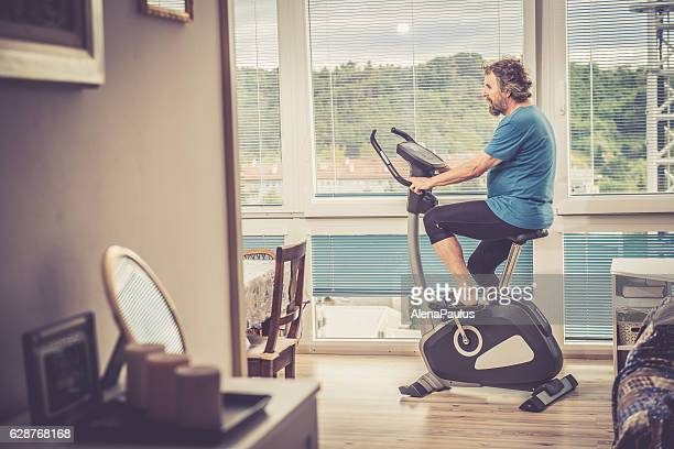 senior man exercising at home - mediterranean active seniors - peloton stock pictures, royalty-free photos & images