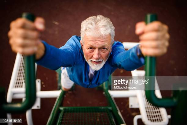 senior man exercising at the park. - chin ups stock photos and pictures