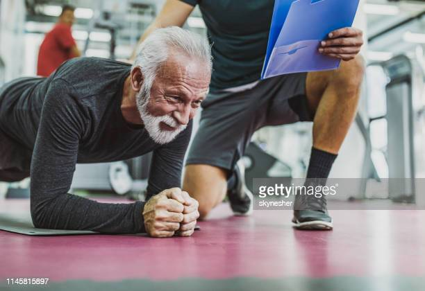 senior man exercising endurance on a training with his coach in a gym. - plank position stock pictures, royalty-free photos & images