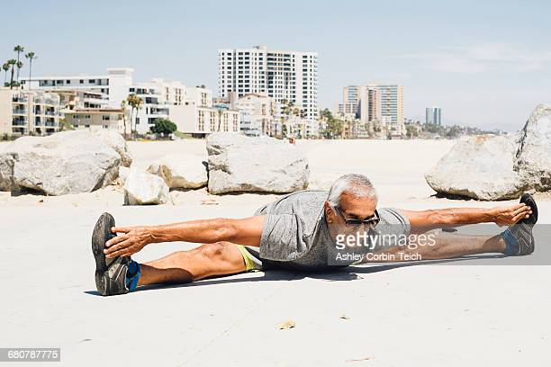 senior man, exercising on beach, stretching, long beach, california, usa - doing the splits stock pictures, royalty-free photos & images