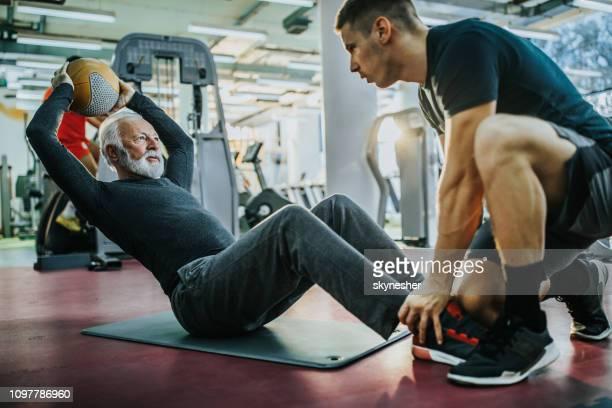 senior woman sit-ups mit hilfe von seinem jungen trainer trainieren. - krafttraining stock-fotos und bilder