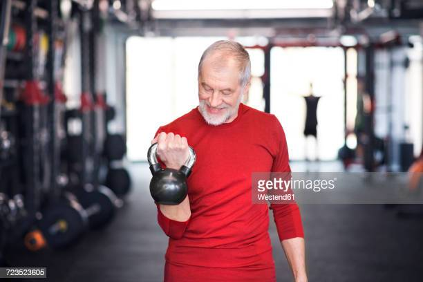 senior man exercising with kettlebell in gym - trainold stock pictures, royalty-free photos & images
