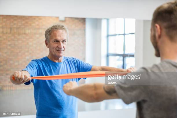 senior man exercising with resistance band at rehab - drug rehab stock pictures, royalty-free photos & images