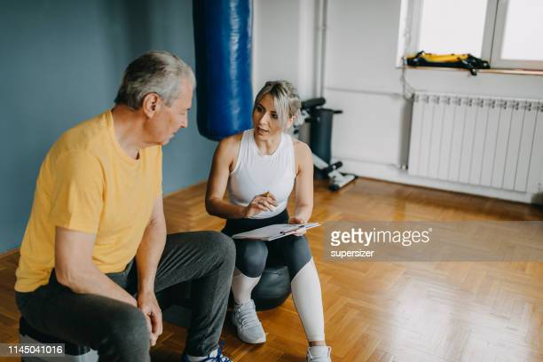 senior man exercising with the assistance from young woman - personal trainer - nutritionist stock pictures, royalty-free photos & images