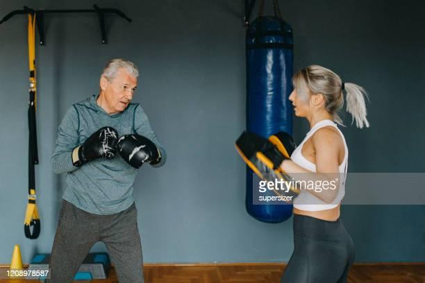 hombre mayor haciendo ejercicio con la ayuda de una mujer joven - entrenador personal - deporte de combate fotografías e imágenes de stock
