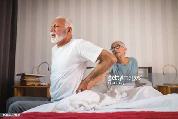senior man experiencing back pain - herniated disc stock pictures, royalty-free photos & images