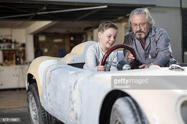 Senior man explaining convertible to boy