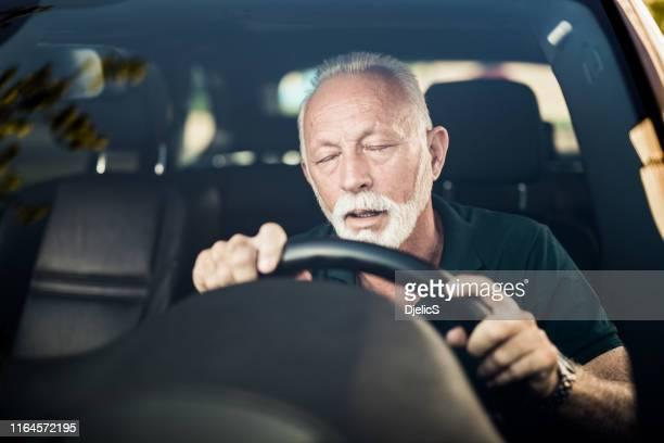車を運転中に眠りに落ちる先輩男性。 - ノックアウト ストックフォトと画像