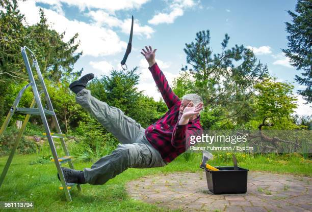 senior man falling from ladder in garden - hinunter bewegen stock-fotos und bilder