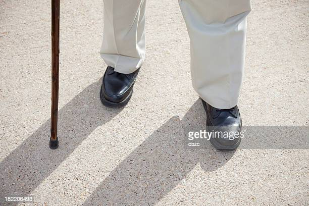 senior man feet and cane walking on sidewalk - walking cane stock photos and pictures