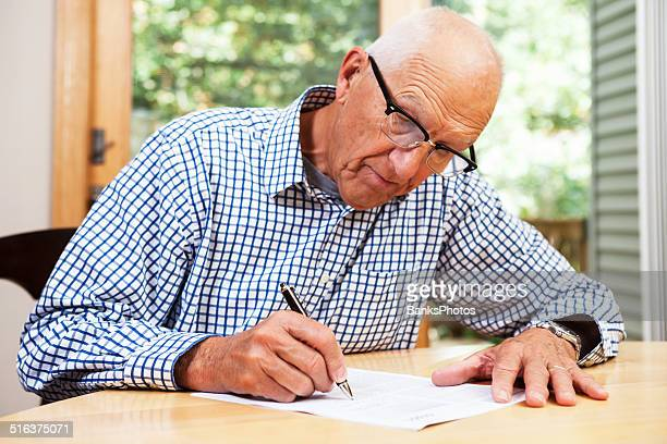 senior man filling out paperwork, signing document - form filling stock pictures, royalty-free photos & images