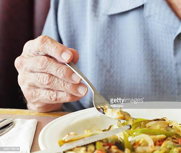 年配の男性手指のクローズアップ、フォークの朝食