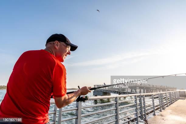 senior mann angeln bei sonnenaufgang. - gulf coast states stock-fotos und bilder