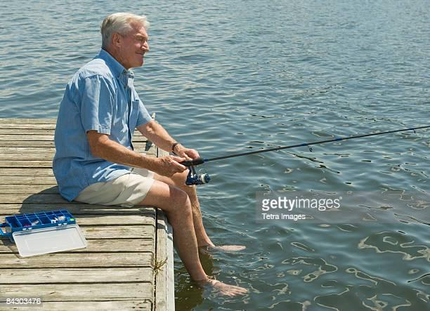 senior man fishing off dock - waterlijn stockfoto's en -beelden