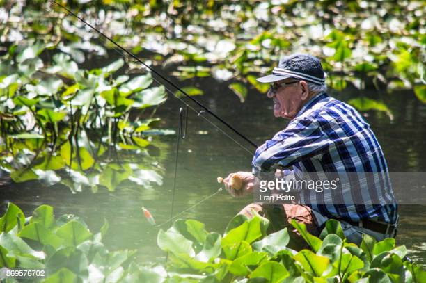 senior man fishing. - baldwin brothers stock photos and pictures