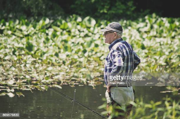 senior man fishing. - baldwin brothers stock pictures, royalty-free photos & images