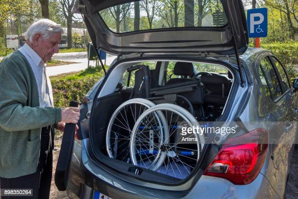Senior man fitting dismantled wheelchair from physically disabled elderly wife in car trunk at parking for handicapped persons
