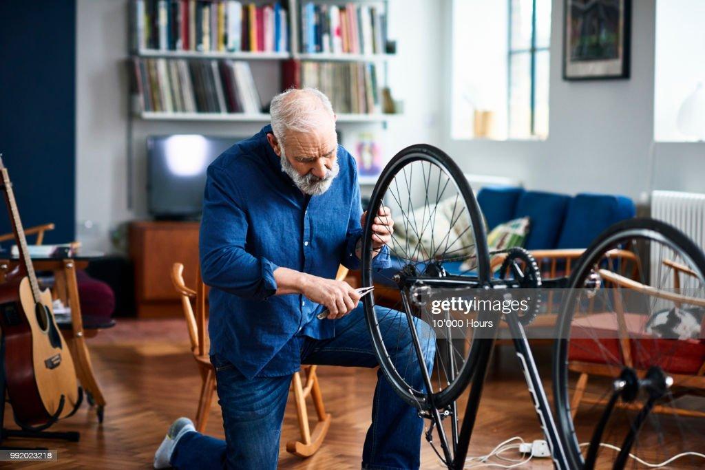 Senior man fixing bike using pliers to repair wheel : Stock Photo