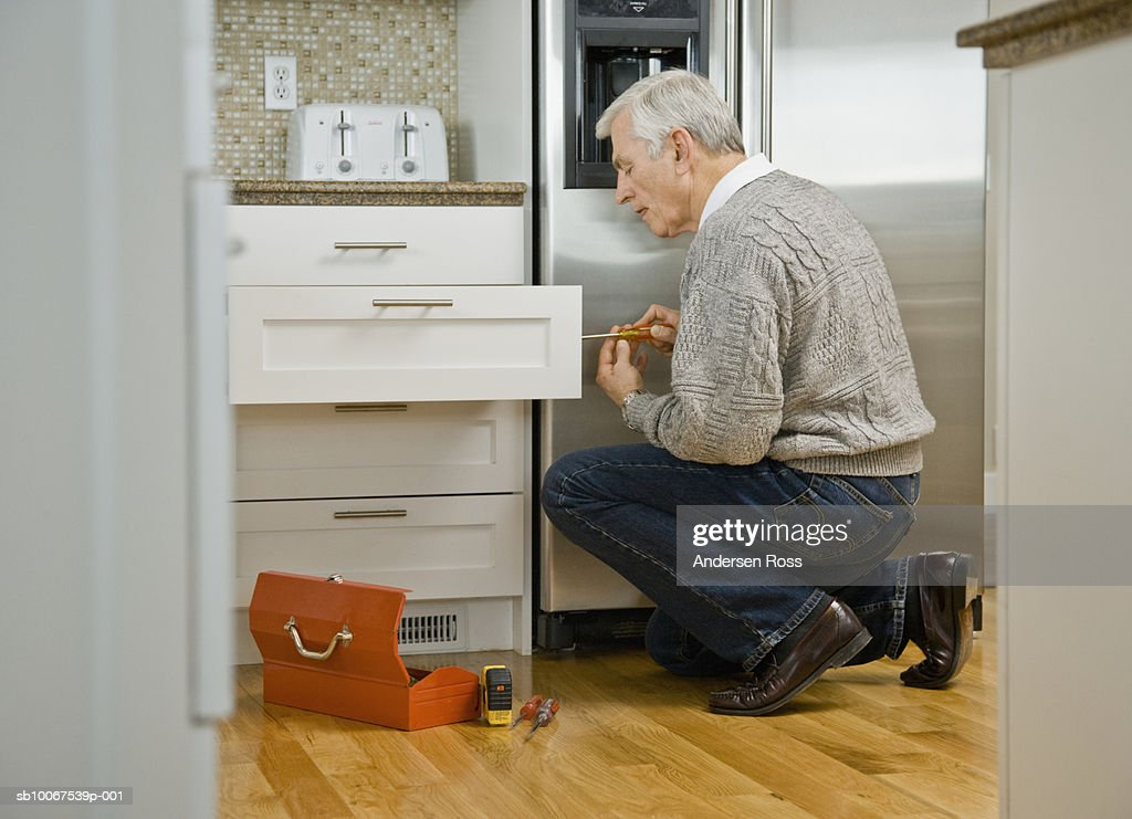 Senior Man Fixing Kitchen Drawer, Side View : Stock Photo