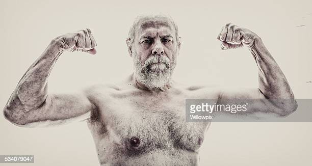 senior man flexing arm muscles - hairy old man stock pictures, royalty-free photos & images