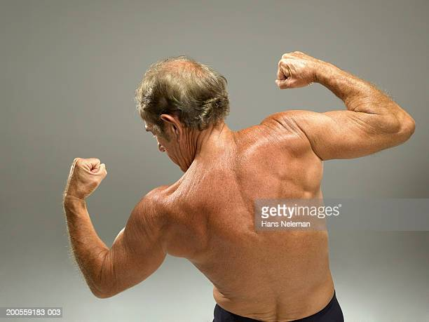 Senior man flexing bicep, close-up