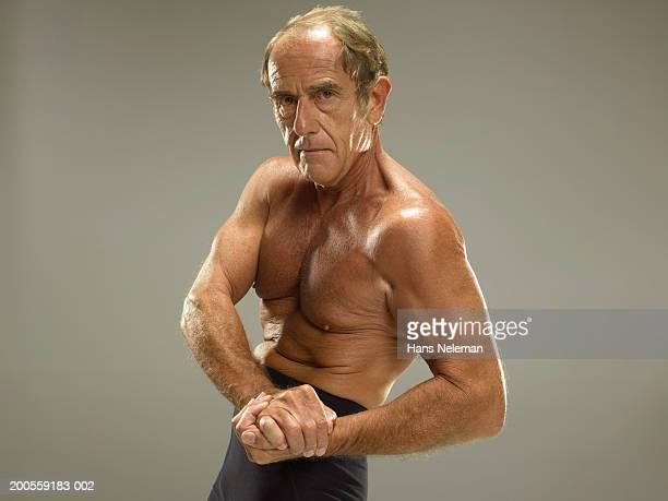 Senior man flexing bicep, portrait