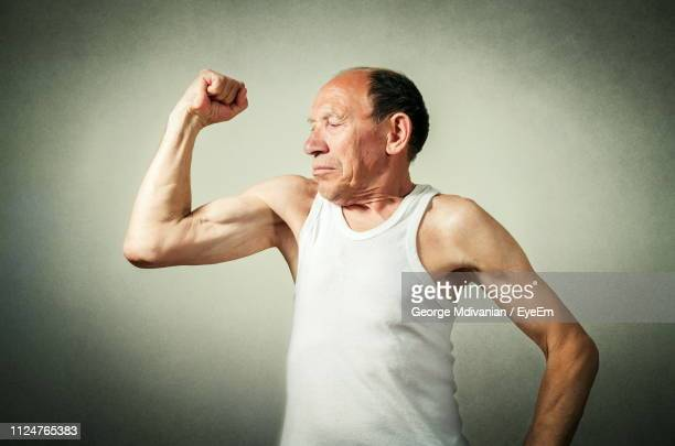 senior man flexing muscles against wall - flexing muscles stock pictures, royalty-free photos & images