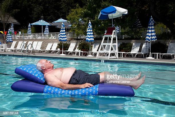 Senior man floating on raft in pool