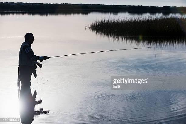 senior man fly fishing - fly casting stockfoto's en -beelden