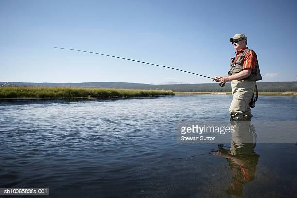 Senior man flyfishing in river