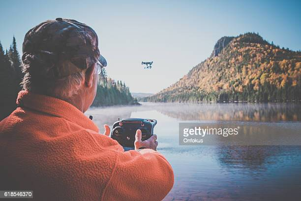 senior man flying a drone in forest - remote control helicopter stock photos and pictures