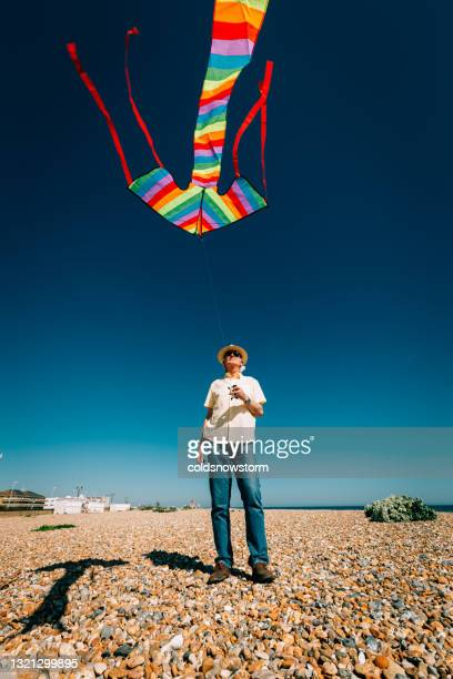 senior man flying colorful rainbow kite at beach - wind stock pictures, royalty-free photos & images