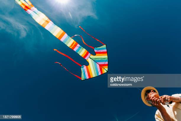 senior man flying colorful rainbow kite at beach - bright colour stock pictures, royalty-free photos & images