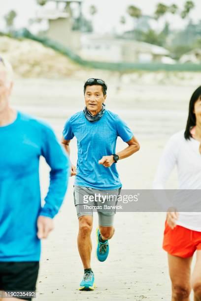 Senior man following friends during early morning run on beach