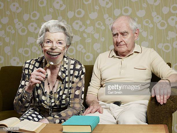 Senior man frowns as senior woman magnifies appearance of her mouth with magnifying glass