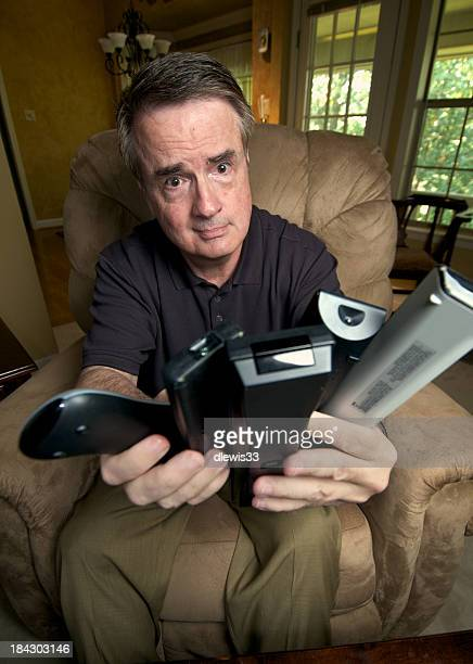 Senior Man Frustrated with Too Many TV Remote Controls