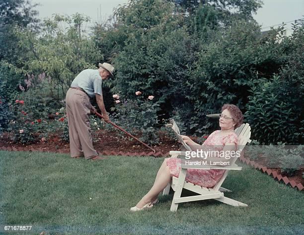 Senior Man Gardening While Senior Woman Reading Newspaper At Backyard
