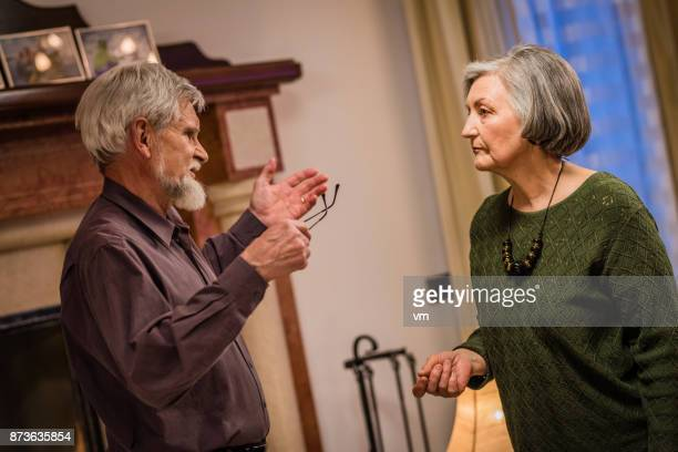 Senior man gesturing angrily at his wife