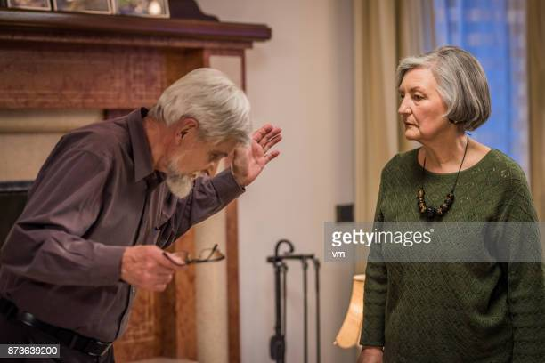 Senior hombre gesticular airadamente a su esposa