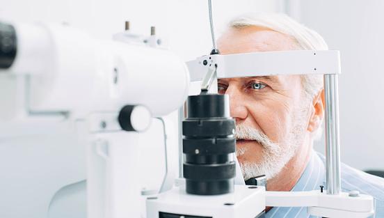 Senior man getting eye exam at clinic, close-up 1055656524
