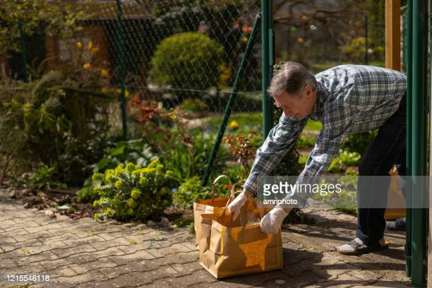 senior man getting food delivery during covid-19 at garden fence - epidemiology stock pictures, royalty-free photos & images
