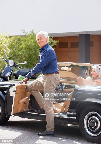 Senior man getting into convertible