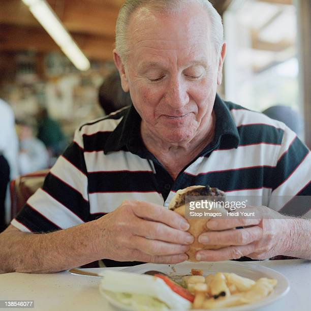 A senior man getting ready to eat a hamburger