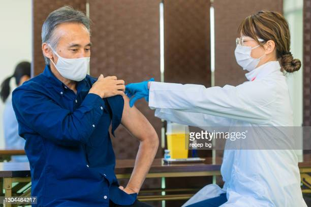 senior man getting vaccinated in vaccination center - vaccination center stock pictures, royalty-free photos & images