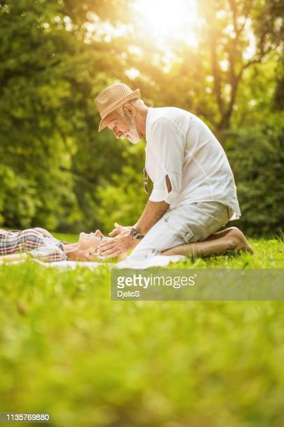 senior man giving a temple massage to his wife while on a picnic in nature. - husband massage wife stock photos and pictures