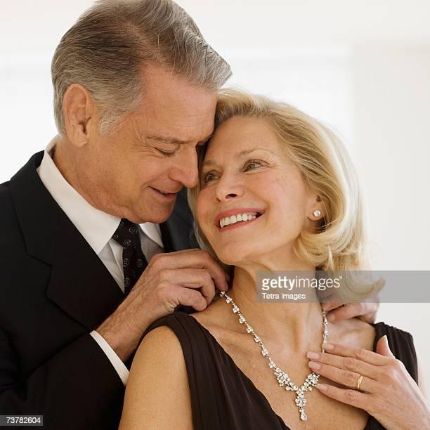 Senior man giving diamond necklace to wife