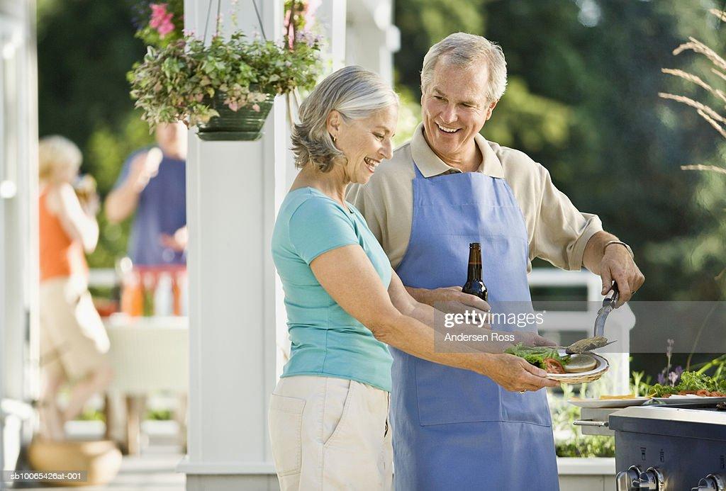 Senior man giving hamburger to senior woman : Foto stock
